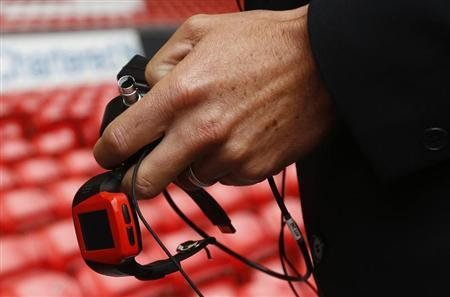 Assistant Referee Lee Probert holds a watch linked to the Hawkeye system before the English Premier League soccer match between Liverpool and Stoke City at Anfield in Liverpool, northern England, August 17, 2013. REUTERS/Darren Staples