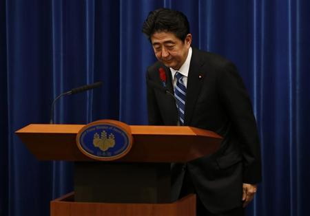 Japan's Prime Minister Shinzo Abe bows at the end of a news conference to announce a raise in the sales tax rate at his official residence in Tokyo October 1, 2013. REUTERS/Toru Hanai