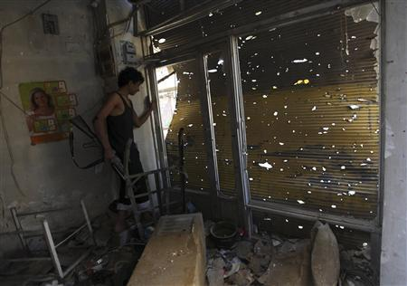 A Free Syrian Army fighter carries his weapon as he peeks out from a damaged shop in Deir al-Zor October 6, 2013. Picture taken October 6, 2013. REUTERS/Khalil Ashawi