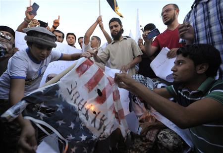 Protesters burn a replica of the U.S. flag during a protest against the capture of Nazih al-Ragye, in Benghazi October 7, 2013. REUTERS/Esam Omran Al-Fetori