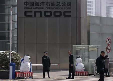 Security personnel stand next to snowmen at the entrance of China National Offshore Oil Corp (CNOOC) office tower in Beijing, March 20, 2013. REUTERS/Petar Kujundzic