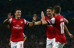 Arsenal's Mesut Ozil (L) celebrates with teammates Olivier Giroud and Aaron Ramsey (R) after scoring a goal against Napoli during their Champions League soccer match at the Emirates stadium in London October 1, 2013. REUTERS/Eddie Keogh