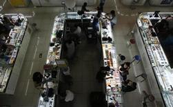 Funcionários negociam com consumidores em cabines que vendem celulares em shopping center em Pequim, China, 3 de setembro de 2013. O crescimento do setor de serviços da China desacelerou em setembro e o otimismo sobre as perspectivas de negócios enfraqueceu, mostrou a pesquisa Índice de Gerentes de Compras (PMI, na sigla em inglês) do Markit/HSBC nesta terça-feira, indicando que a recuperação nascente na segunda maior economia do mundo deve seguir lenta. 03/09/2013 REUTERS/Kim Kyung-Hoon