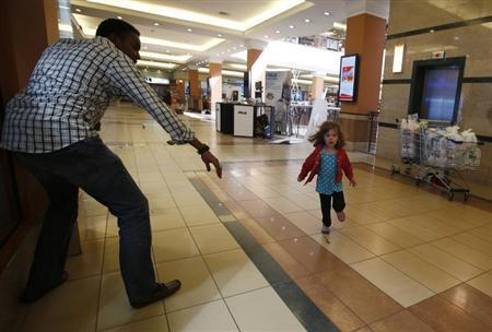 A child runs to safety as armed police hunt gunmen who went on a shooting spree at Westgate shopping centre in Nairobi September 21, 2013. REUTERS/Goran Tomasevic
