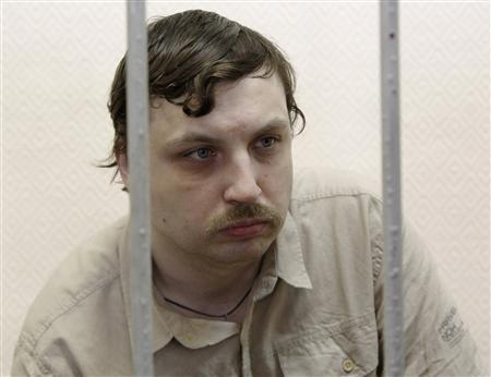 Mikhail Kosenko sits inside a defendants' cage during a court hearing in Moscow May 29, 2013. REUTERS/Maxim Shemetov