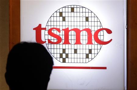 A man sits in front of the logo of Taiwan Semiconductor Manufacturing Co Ltd (TSMC) during an investors' conference in Taipei in this April 18, 2013 file photo. REUTERS/Pichi Chuang/Files