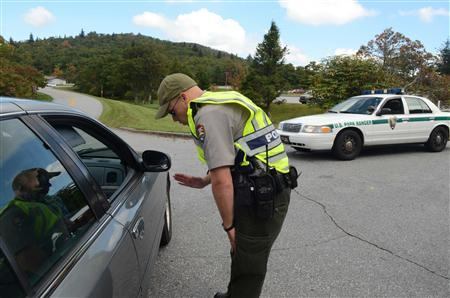 Park Ranger Joseph Darling directs visitors away from the entrance to the Pisgah Inn on the Blue Ridge Parkway southwest of Asheville, North Carolina, October 4, 2013. REUTERS/Dillon Deaton/Asheville Citizen-Times/Handout via Reuters