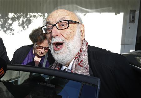 Belgian physicist Francois Englert reacts as he leaves his house with his wife Mira in Brussels October 8, 2013, after he and Britain's Peter Higgs won the 2013 Nobel prize for physics. REUTERS/Yves Herman