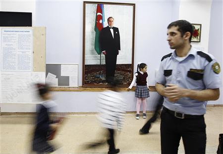 An election official looks on as children play in front of a portrait of Heydar Aliyev, Azerbaijan's late president and father of current President Ilham Aliyev, at a polling station located inside a school in Baku, October 8, 2013. REUTERS/David Mdzinarishvili
