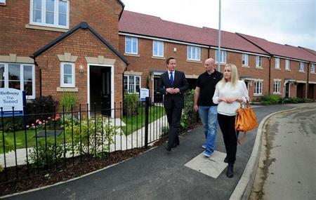 Britain's Prime Minister David Cameron (L) speaks to first time buyers Kayleigh Groom (R) and her partner Chris Day during a visit to Weston Favell in Northampton, central England October 8, 2013. REUTERS/Rui Vieira/Pool