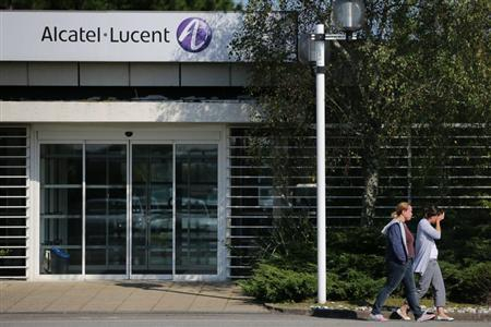 Employees of Alcatel-Lucent walk past an entrance at the company site in Orvault near Nantes, western France, October 8, 2013. REUTERS/Stephane Mahe