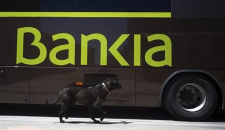 A dog walks past a bank bus during its monthly call on customers in the village of Corral de Ayllon, central Spain, June 4, 2013. REUTERS/Sergio Perez