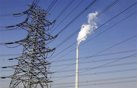 A chimney billows smoke behind electricity wires in central Beijing December 21, 2009. REUTERS/David Gray