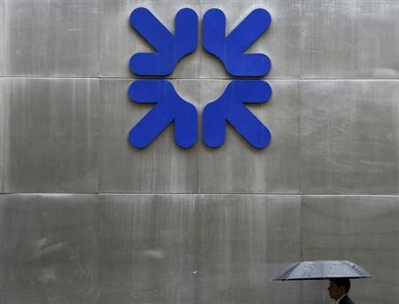 A man shelters under an umbrella as he walks past a branch of the Royal Bank of Scotland in the City of London September 17, 2013. REUTERS/Stefan Wermuth