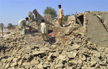 Survivors collect their belongings from the rubble of a mud house after it collapsed following an earthquake in the town of Awaran, southwestern Pakistani province of Baluchistan, September 25, 2013. REUTERS/Naseer Ahmed