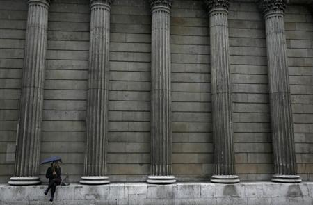 A woman sheltering under an umbrella sits outside the Bank of England in the City of London September 17, 2013. REUTERS/Stefan Wermuth