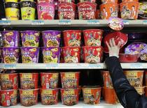 A woman chooses a cup noodle from a shelf displaying cup noodles from Uni-President China (top and middle) and Tingyi (bottom) at a supermarket in Beijing October 9, 2013. REUTERS/Kim Kyung-Hoon