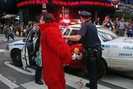 Dan Sandler, dressed as the Muppet character Elmo, is handcuffed and detained by police after using anti-Semitic language in Times Square, New York, in this file picture taken September 18, 2012. REUTERS/Adrees Latif/Files