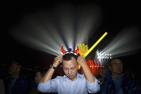 Jonathan Lu, new chief executive of Alibaba Group, puts on a headband with horns during the celebration of the 10th anniversary of Taobao Marketplace, China's largest consumer-focused e-commerce website, in Hangzhou, May 10, 2013. REUTERS/Chance Chan