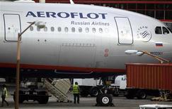 Сотрудники аэропорта у самолета Аэрофлота Москва-Гавана в Гаване 11 июля 2013 года. Государственный авиаперевозчик Аэрофлот снизил чистую прибыль в 4,7 раза до $1,5 миллиона в первом полугодии 2013 года, сообщила компания в четверг. REUTERS/Desmond Boylan