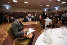 Una mujer presenta una aplicación de empleo en una feria laboral en Nueva York, jun 11 2013. El número de estadounidenses que presentaron nuevas solicitudes de subsidios por desempleo subió la semana pasada a su máximo nivel en seis meses en medio de un fallo computacional en el estado de California, pero la tendencia subyacente apuntaba a una mejoría sostenida en el mercado laboral. REUTERS/Lucas Jackson