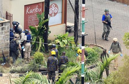 Foreign forensic experts, flanked by Kenyan military personnel, check the perimeter walls around Westgate shopping mall in Nairobi September 25, 2013. REUTERS/Noor Khamis