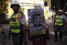 """Un estudiante de la Universidad de Sao Paulo sostiene un póster con fotos del soldado detenido por filtración de datos de Estados Unidos Bradley Manning, el ex contratista de la Agencia Nacional de Seguridad Edward Snowden y el fundador de WikiLeaks Julian Assange (de izquierda a derecha) durante una manifestación en contra del gobernador del estado de Sao Paulo, Geraldo Alckmin, 9 de octubre del 2013. En el cartel se lee en portugués """"Libertad para Snowden"""" y """"Democracia en las calles y en las redes sociales"""". REUTERS/Nacho Doce"""