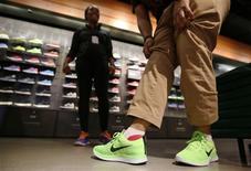 Un hombre se prueba unos zapatos en una tienda de Nike en Santa Monica, sep 25 2013. Los estadounidenses siguieron mostrando cautela en sus gastos durante septiembre, aunque algunos se vieron atraídos por las ofertas, en momentos en que la disputa política en Washington y la débil creación de empleo afectaban la confianza cuando faltan semanas para el inicio de la temporada de compras de fin de año. REUTERS/Lucy Nicholson