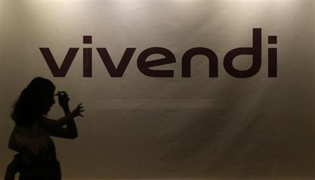 A woman holding a young girl in her arms is silhouetted as she walks past the main entrance of the entertainment-to-telecoms conglomerate Vivendi's headquarters in Paris, August 28, 2013. REUTERS/Christian Hartmann