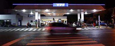 Un vehículo pasa frente a una gasolinera de la estatal YPF en Buenos Aires, abr 16 2012. El Gobierno argentino dispuso el jueves extender en 45 días un congelamiento en los precios máximos de los combustibles que había dispuesto a mediados de abril pasado, en una medida para contener la alta inflación en el país en momentos en que se enfrenta a unas elecciones legislativas claves. REUTERS/Marcos Brindicci