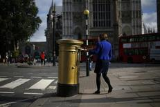 A woman post a letter into a golden Royal Mail post box in central London, October 8, 2013. REUTERS/Andrew Winning