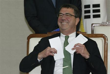 U.S. Deputy Secretary of Defence Ashton Carter holds letters before talks with South Korean Defence Minister Kim Kwan-jin (not pictured) at the defence ministry of South Korea in Seoul March 18, 2013. REUTERS/Lee Jae-Won