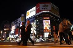 People walk along a pedestrians' crossing at Susukino shopping and amusement district in Sapporo, on Japan's northern island of Hokkaido October 9, 2013. REUTERS/Nathan Layne