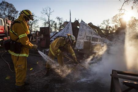 Shasta County firefighters Zach Lacy (L) and Bob Baker spray water on a home burnt by the Clover Fire in Happy Valley, California September 10, 2013. REUTERS/Max Whittaker