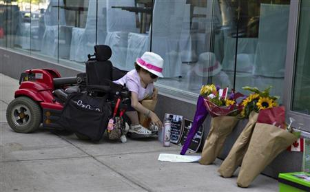 Amelia Cooper places a card at a small memorial to Canadian actor Cory Monteith outside the Fairmont Pacific Rim hotel in Vancouver, British Columbia July 15, 2013. REUTERS/Andy Clark
