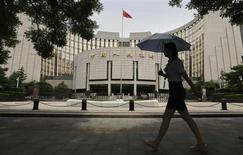Женщина проходит мимо Банка Китая в Пекине 21 июня 2013 года. Экономический рост Китая должен превысить 7,5 процента в этом году, сказал заместитель управляющего Центробанка И Ган, вновь подтвердив, что вторая по величине экономика мира стабилизируется. REUTERS/Jason Lee