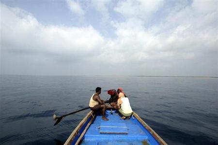 Fishermen sit on a boat in the Bay of Bengal near Gundalaba village, about 100 km (62 miles) east from Bhubaneswar, March 14, 2007. REUTERS/Parth Sanyal/Files