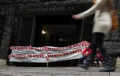 Mulher caminha em frente à entrada do Banco do Brasil bloqueada por bancários em greve, em São Paulo. Os bancos no Brasil aceitaram elevar oferta de reajuste salarial nesta sexta-feira, e bancários parados há 23 dias poderão retornar ao trabalho a partir da próxima segunda-feira, informou confederação dos trabalhadores do setor. 19/09/2013. REUTERS/Paulo Whitaker