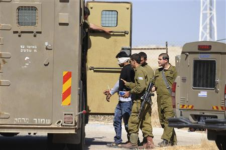 Israeli soldiers detain a Palestinian close to the scene where Sariya Ofer, a retired Israeli army officer was killed in the West Bank Jewish settlement of Brosh Habika in the Jordan Valley October 11, 2013. REUTERS/Gil Eliyahu/JINIPIX