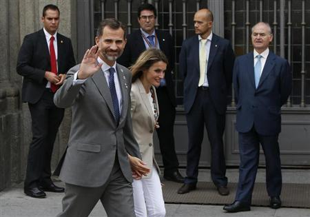 Spain's Princess Letizia and her husband, Spain's Crown Prince Felipe, walk away after she collected money donations for the Spanish Red Cross during ''Fiesta de la Banderita'' in Madrid October 3, 2013.REUTERS/Susana Vera
