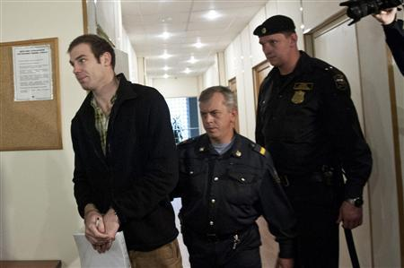 Briton Kieron Bryan, a Greenpeace International commissioned freelance videographer, is led to a bail hearing at the Regional Court of Murmansk October 11, 2013. REUTERS/Dmitri Sharomov/Greenpeace/Handout via Reuters