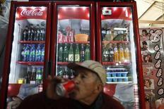 Un hombre bebe una gaseosa al interior de una tienda en Ciudad de México, sep 9 2013. En México, uno de los países con mayores problemas de obesidad de la región, las empresas de refrescos y del negocio de la caña están luchando a capa y espada por bloquear una iniciativa para gravar las bebidas azucaradas. REUTERS/Edgard Garrido