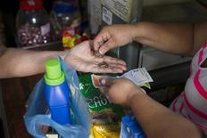 Un cliente recibe su cambio de manos de una cajera en un supermercado en Caracas, feb 14 2013. Venezuela reactivará a partir de la próxima semana su Sistema Complementario de Administración de Divisas (Sicad), en un intento por aliviar la sed de dólares que ha presionado la inflación y generado episodios de escasez. REUTERS/Carlos Garcia Rawlins