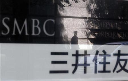 A security guard is reflected on a sign outside a branch of Sumitomo Mitsui Banking Corporation in Tokyo in this July 30, 2012 file photo. REUTERS/Yuriko Nakao/Files