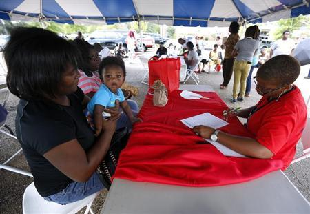 Lisa Smith (R) helps uninsured Danielle Winters (L) and her 7-month-old grandson Tyler, who is on medicare, sign up for the Affordable Care Act, or ''Obamacare'', outside the Jackson-Hinds Comprehensive Health Center in Jackson, Mississippi October 4, 2013. REUTERS/Jonathan Bachman