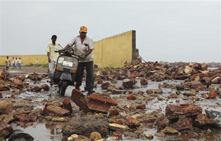 People walk among debris from a broken wall after it was damaged by a wave brought by Cyclone Phailin at a fishing harbour in Visakhapatnam district in the southern Indian state of Andhra Pradesh October 12, 2013. REUTERS/R Narendra