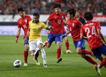 Neymar disputa a bola com jogadores da Coreia do Sul durante amistoso no estádio da Copa do Mundo, em Seul. Neymar e Oscar conferiram em cada uma das etapas na vitória tranquila por 2 x 0 do Brasil sobre a Coreia do Sul no amistoso deste sábado, no qual os anfitriões da Copa do Mundo de 2014 imperaram. 12/10/2013. REUTERS/Kim Hong-Ji
