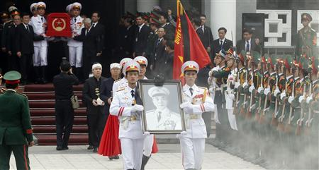 Soldiers hold up the portrait of the late General Vo Nguyen Giap as his coffin is carried during his funeral at the National Funeral House in Hanoi October 13, 2013. REUTERS/Kham