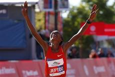 Rita Jeptoo of Kenya celebrates as she crosses the finish line to win the women's division at Chicago Marathon in Chicago, Illinois, October 13, 2013. REUTERS/Jim Young