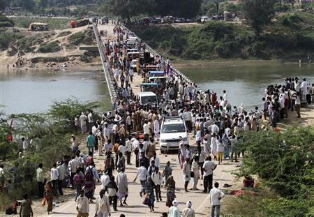 People cross a bridge after a stampede near Ratangarh temple in Datia district in the central Indian state of Madhya Pradesh October 13, 2013. REUTERS/Stringer